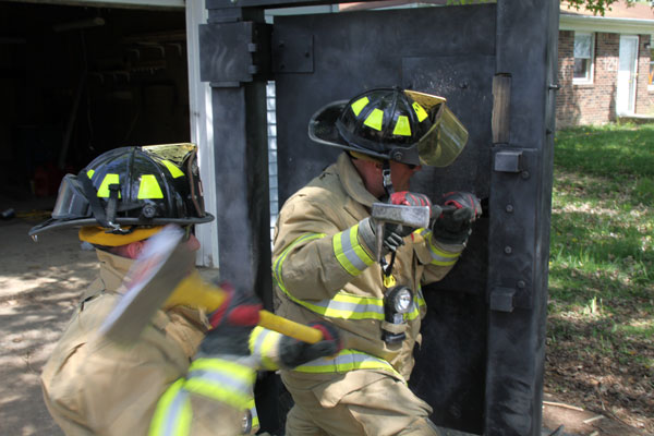 Firefighters perform forcible entry on a training prop.