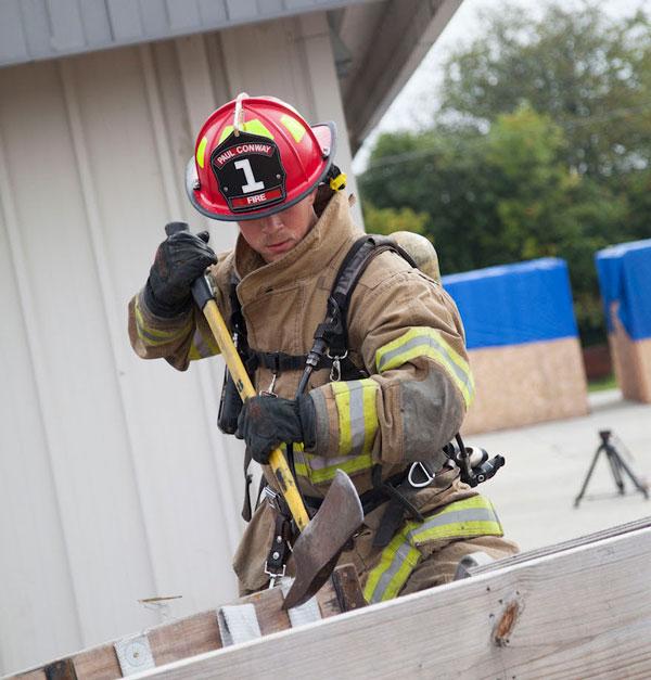 A firefighter wields an ax.