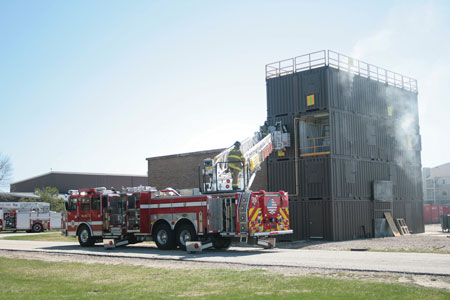 (2) In a multicompany live fire evolution, a tower ladder from one department is used for upper-level access while different fire departments advance hoselines on the interior.