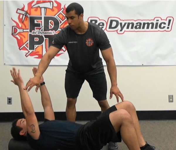 Jordan Ponder and a firefighter perform the Dead Bug exercise.