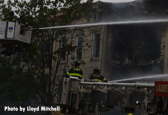 Tower ladders operating at the scene of a gas explosion that collapsed a three-story building in Brooklyn.