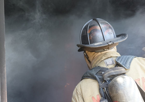 A firefighter proceeds into a smoky compartment.