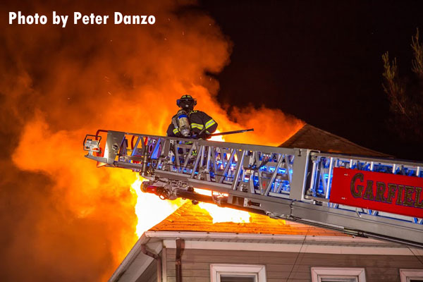 A firefighter on an aerial device as fire vents through the roof at a Garfield house fire.