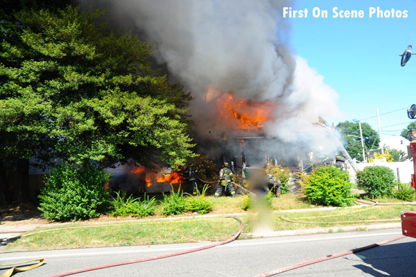 Firefighters conduct suppression operations at a house fire in Hempstead, New York.