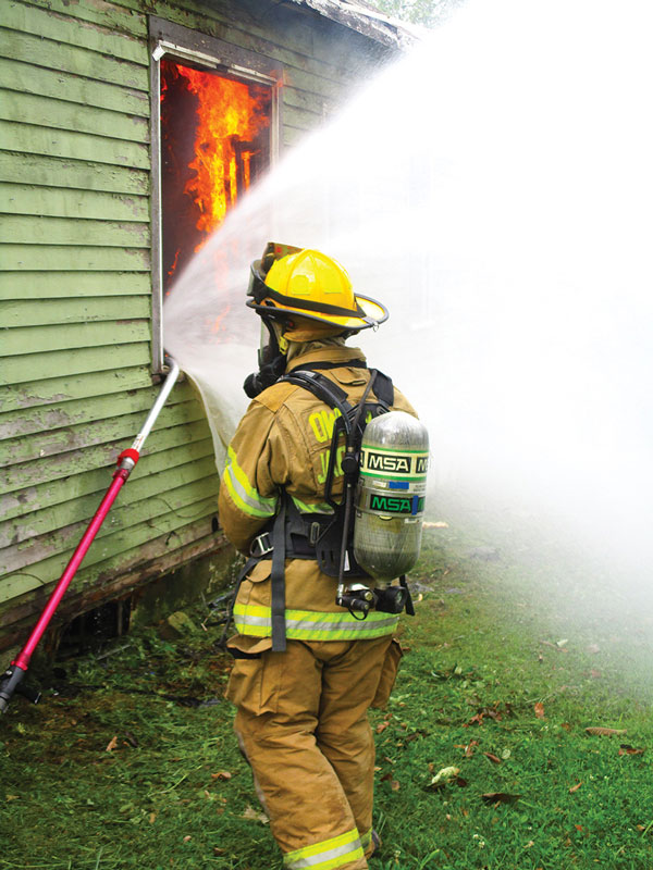 Firefighter using HydroVent at a structure fire.