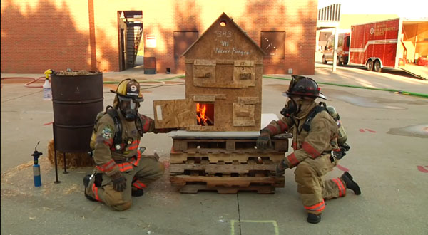 Firefighter manipulate the openings on a so-called dollhouse to simulate various fire behavior scenarios.