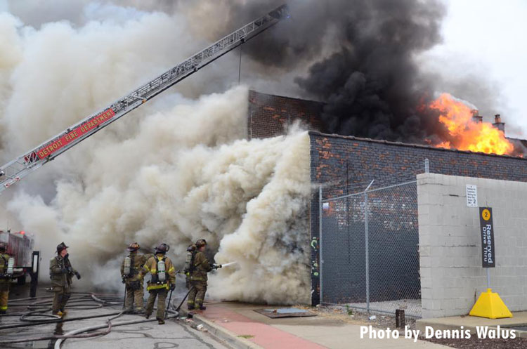 Smoke pours from a building and flames are seen in another part of the structure as Detroit fire companies operate defensively.