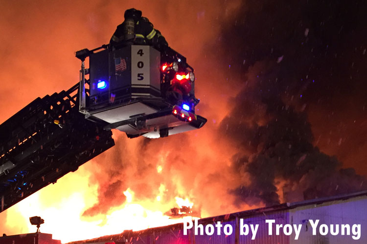 Firefighter in a tower ladder bucket overseeing a massive mill fire in New York.