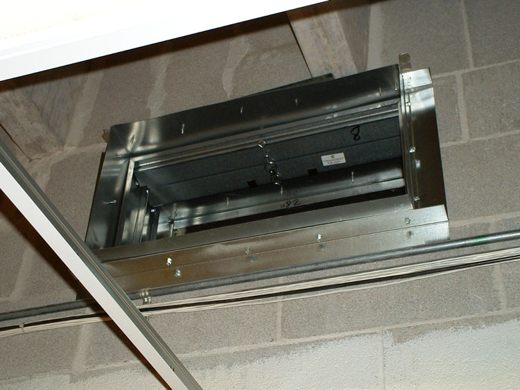 A fire damper unit that has been installed in a two-hour-rated masonry wall.