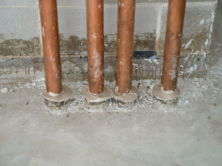 Four pipes penetrating a two-hour-rated structural concrete floor, each with its own steel pipe sleeve.