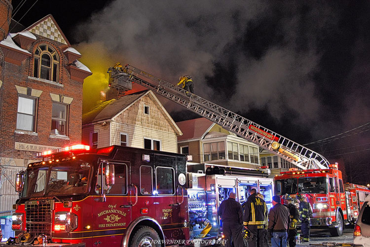 Firefighters and apparatus at the scene of a house fire in Mechanicville, New York.