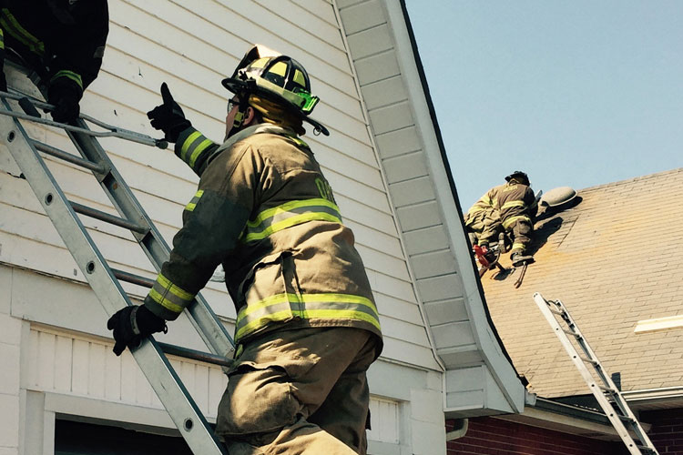 A firefighter reaches up a ladder while others perform roof work.