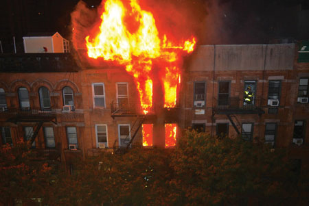 (1) The amount of fire visible on the top two floors and roof indicates the large volume of fire that members had to deal with at this building fire. <i>(Photos 1-7 by Lou Minutoli.) </i>