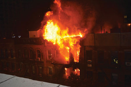 (2) The amount of fire visible in front and the flames visible over the roof in the rear of the building indicate that the apartments were fully involved front to rear.
