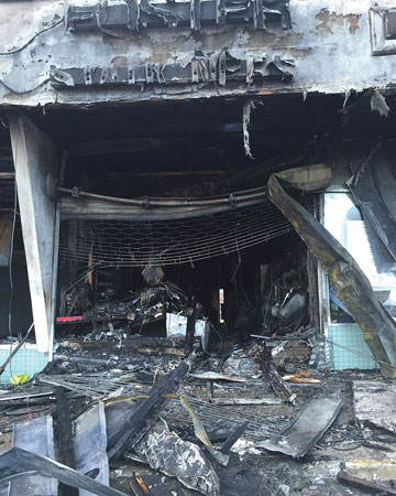 (4) The storefront after knockdown shows a mangled roll-down gate and debris from the collapsed soffit that had to be overcome during the fire attack.<i> (Photo by Jason Lanzilotti.) </i>