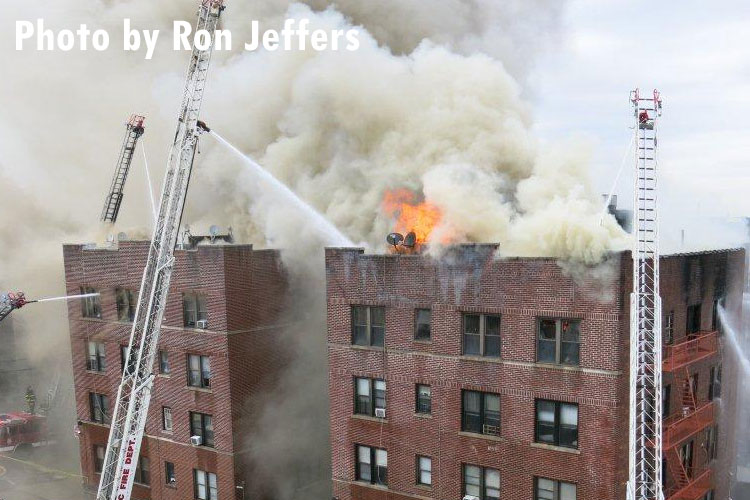 Multiple master streams and aerial devices pour water on a fire in an apartment building in Passaic as flames vent through the roof.