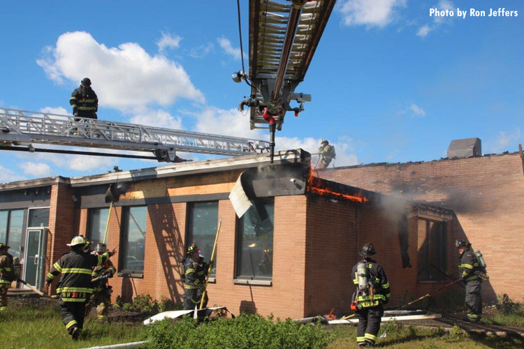 Firefighters work to contain a fire in a building that was sparked by a plane crash in Carlstadt, New Jersey.