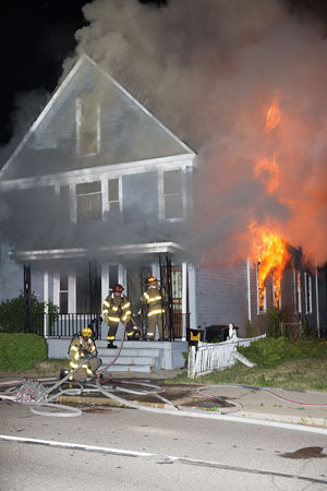 (<b>1-3)</b> First-arriving firefighters find a heavy fire condition on the first floor of what appears to be a 2½-story wood-frame dwelling with fire extending to the second floor and attic half-story. <i>(Photos by Gordon Nord.)</i>