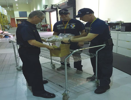 (2) Assistant Chief Todd Leduc and BCSDFR firefighters overpacking soiled hoods for advanced testing.