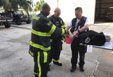 """(4) Battalion Chief James Quinn and his crews demonstrating the hood exchange program and """"hazardous overpacking"""" of contaminated hoods before being sent for advanced cleaning. (Photo by Todd Leduc.)"""
