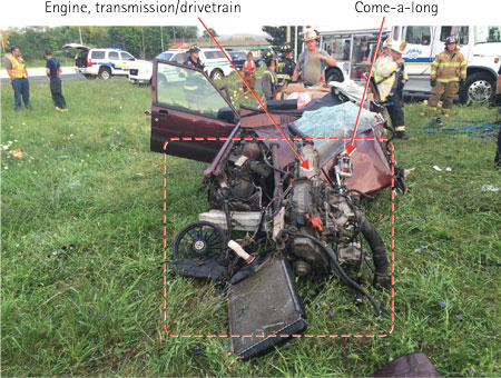 ((3) The force of the impact into the tree dislodged the entire engine, transmission/drivetrain completely from the engine compartment. Note the come-a-long setup at the front vehicle hood (arrows).