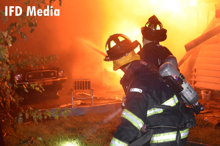 Firefighters on a hoseline work to protect an exposure building