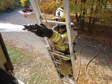 """(1) The hose is properly secured with two hose straps using the """"in-and-out"""" method of rigging. The strap is lashed to the hose, then extended upward inside the ladder toward the building and then brought outside the ladder away from the building and hooked over the rung two rungs up. The firefighter is using a leg lock on the side opposite of the hoseline. <i>(Photos by author.) </i>"""" id=""""cq-gen1738″></td> </tr> <tr> <td align="""