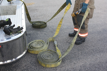 (4) The firefighter is preparing to deploy 150 feet of line. He lays the three rolls on the ground and grabs the coupling between the second and third shot of hose. The nozzle is in his other hand.