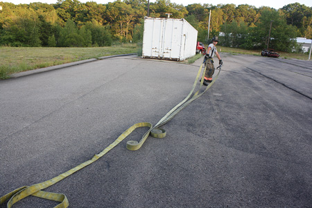 <b>(5-6)</b> The firefighter walks out holding the nozzle and coupling. As the hose unrolls, he will drop the coupling and continue to walk the nozzle to the fire.