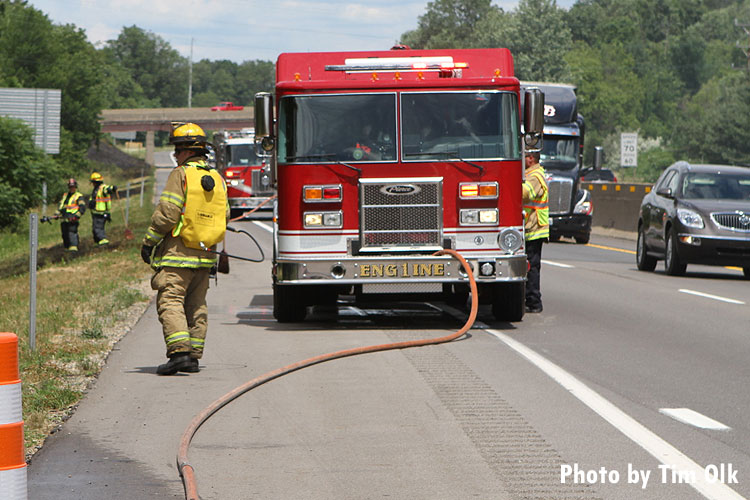 Firefighters on roadway with fire apparatus
