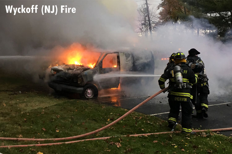 Firefighters train a hosestream on a burning vehicle