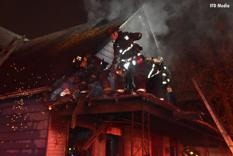 Firefighters work on a porch roof during fire operations at a house fire