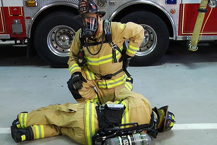 Firefighter peforms buddy breathing technique on a down colleague