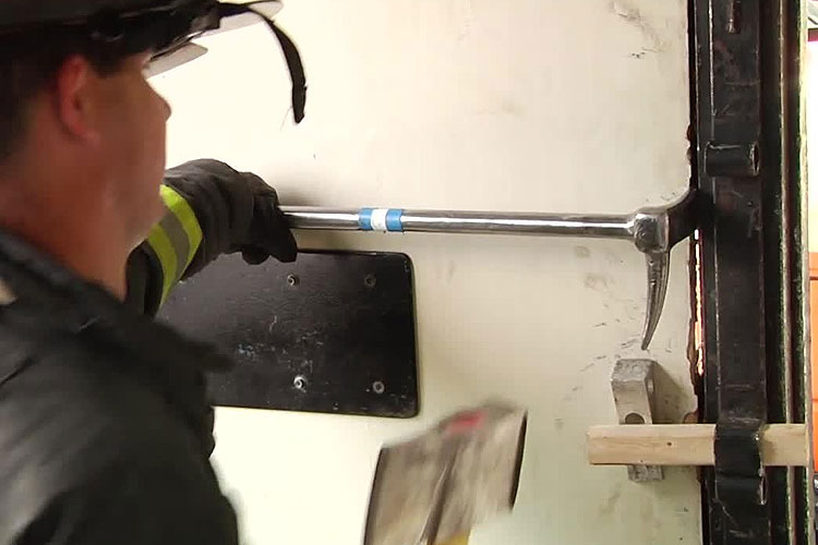 Firefighter using a halligan to force entry on a door