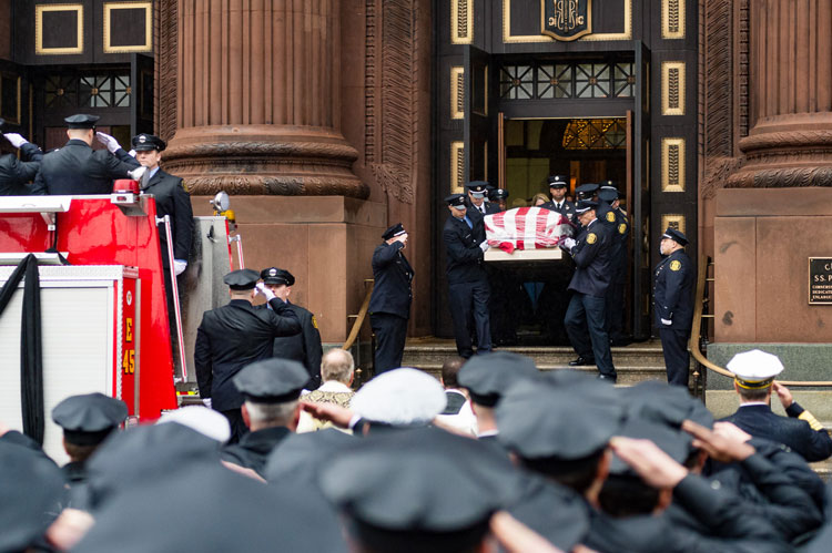 Casket bearing the body of Lt. Matthew LeTourneau is brought to be loaded onto a fire apparatus
