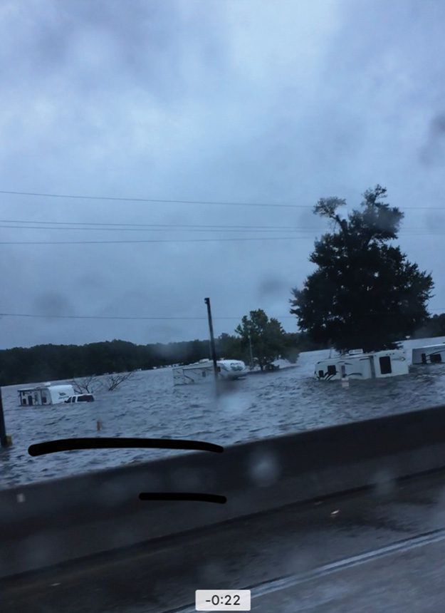 (2) The flooded Ten-Mile Creek swallows trailers, mobile homes, cars, and businesses just off Interstate 10.