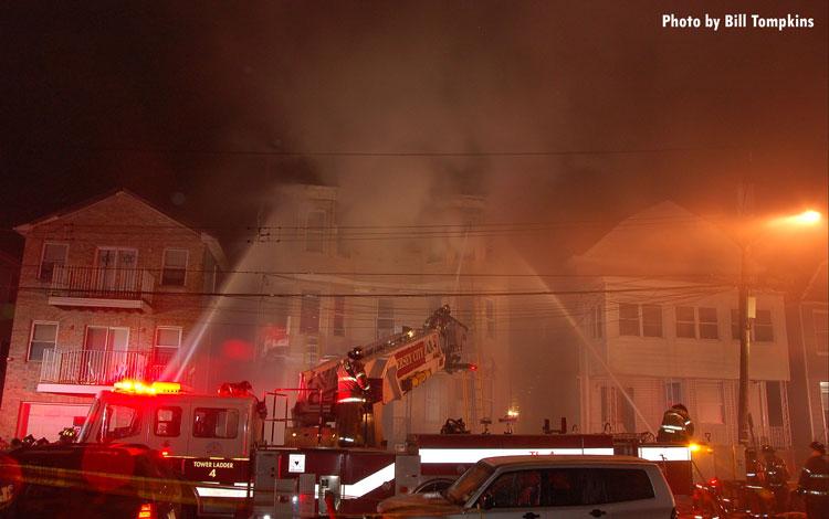 Firefighters train streams on a fire in Jersey City