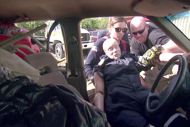 Rescuers remove a dummy patient from a hoarder vehicle during training