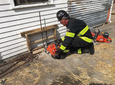 (1) When faced with low cutting operations, a firefighter can use his foot to help support the saw, which also takes some of the vibration off his arms while cutting. (Photos by Josh Materi.)