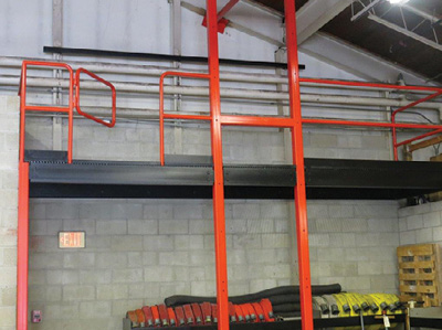 """(7) A permanent ladder would have impacted the exit access to the door. We use a 10-foot A-frame ladder for training periods and tie it off to the platform. The gate closes and latches for safety, and there are """"toe kick"""" plates on the edge. Note the black steel bar welded to the back wall for tying off and hauling."""