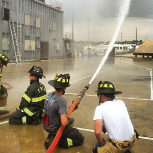 """(1) Thepositioning of the firefighter's rear hand allows for the hoseline to be """"pinned"""" up against the firefighter's hip toassist in resisting the nozzle reaction forces. (Photos courtesy of Brian Brush.)"""