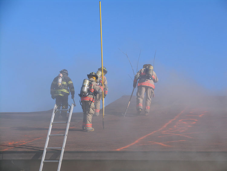 Firefighters cutting holes in a roof