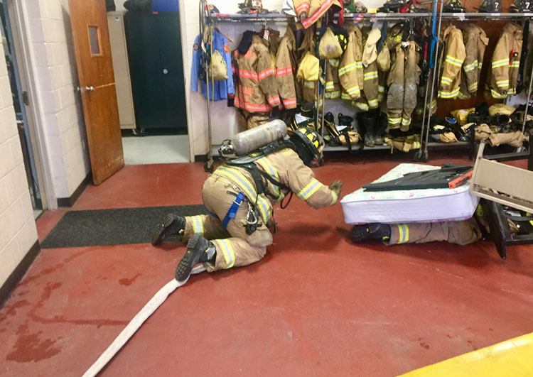 Firefighter follows hoseline to locate down firefighter