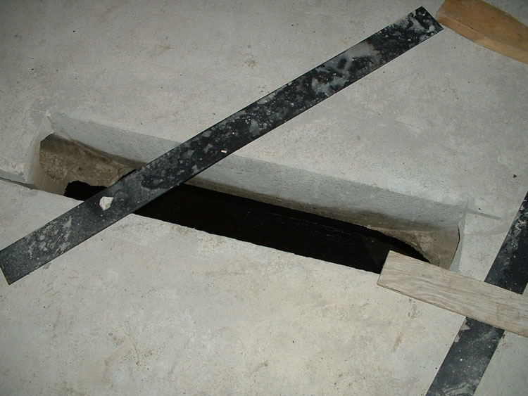 An opening in a precast concrete plank subfloor
