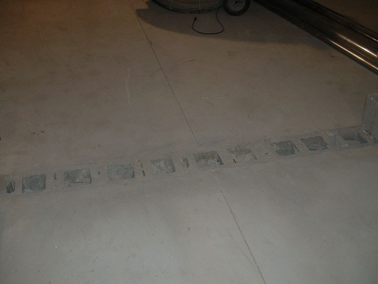 Concrete floors that have been poured flush with the top of a wall of concrete masonry units