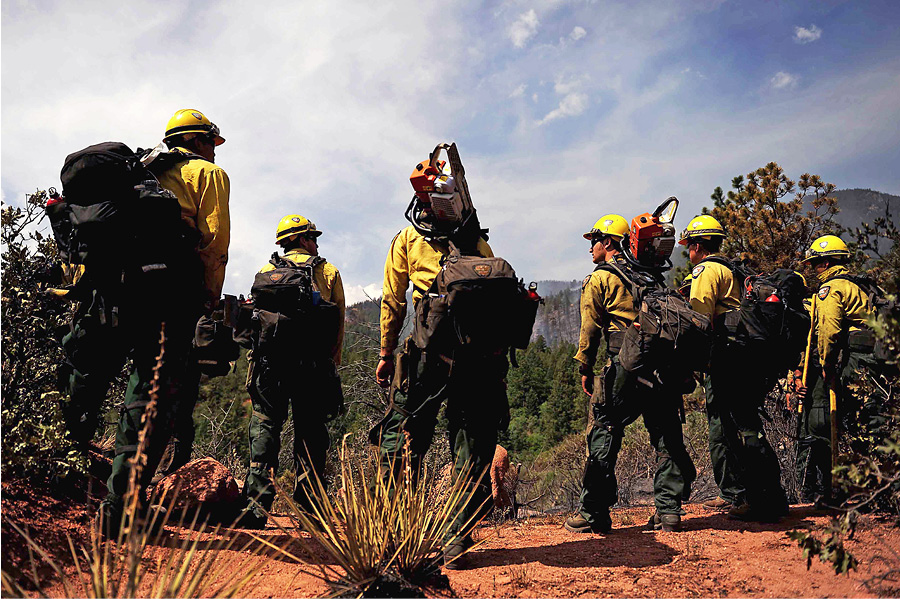 Members of the Hotshots from Vandenberg (CA) Air Force Base prepare to cut a fire line in the Peregrine neighborhood of Colorado Springs, Colorado, in 2012.