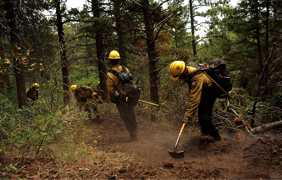 Firefighters from the Vandenberg (CA) Air Force Base Hotshots cut a fire line in the Mount Saint Francois area of Colorado Springs, Colorado, while helping to battle several fires in Waldo Canyon in 2012.