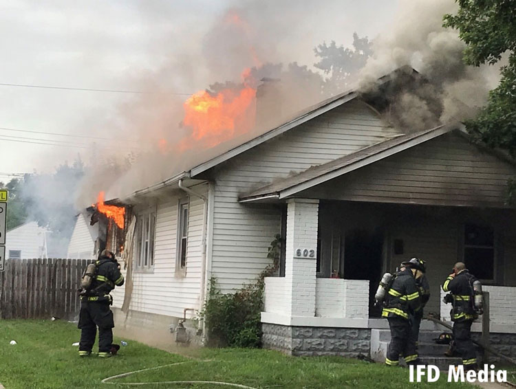 Firefighters attack flames in a burning home