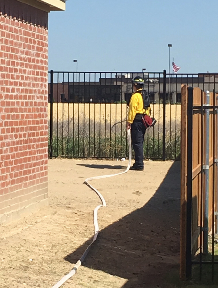 """A firefighter is positioned with a hose to perform the """"bump and run"""" tactic. Note that he is in full personal protective equipment."""