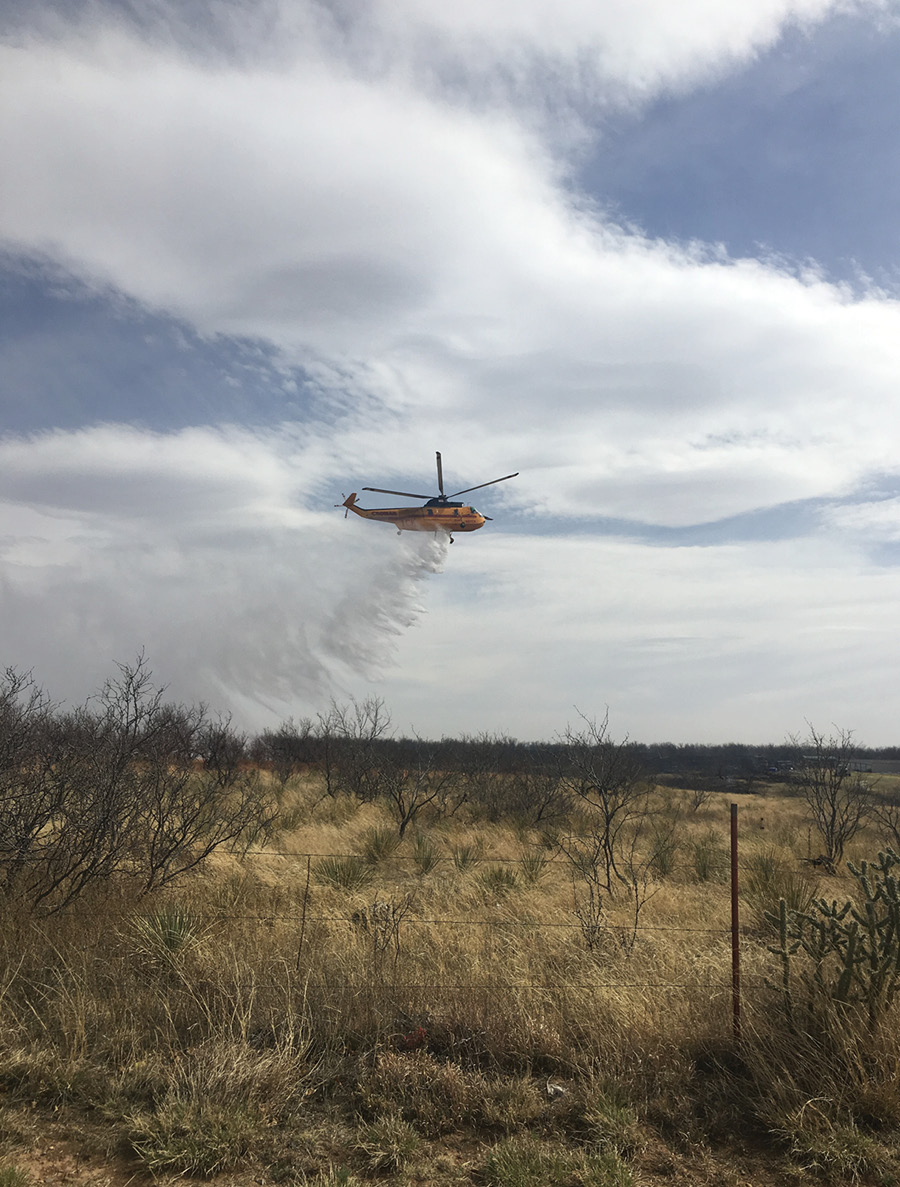 A helicopter drop on the Fritch Fire supports the efforts of the ground force.